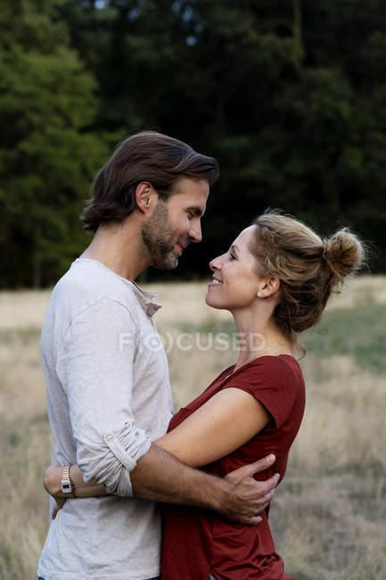 Glückliches Paar in der Natur, von Angesicht zu Angesicht stehend, einander streichelnd — Stockfoto