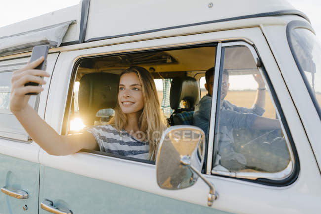 Smiling woman taking a selfie in a camper van with man driving — Stock Photo
