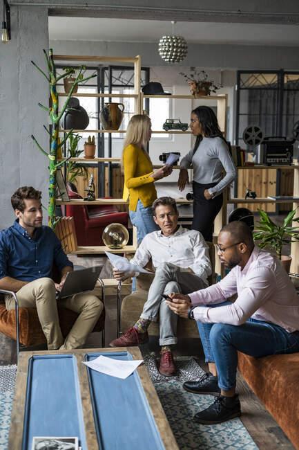 Equipo de negocios que celebra una reunión informal en la oficina de loft - foto de stock