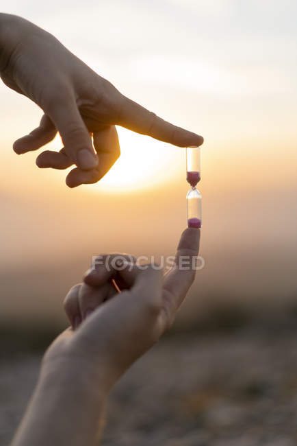 Close-up of male hands holding an hourglass at sunset — Stock Photo