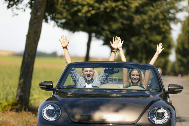 Happy couple driving with raise arms in convertible car on a country road — Stock Photo