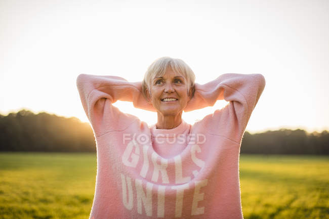 Portrait of confident senior woman standing on rural meadow at sunset — Stock Photo