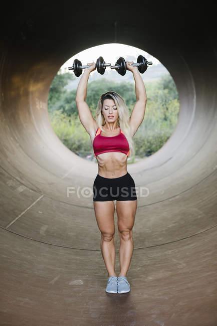 Mujer atlética haciendo ejercicio de peso y de pie dentro de un tubo - foto de stock