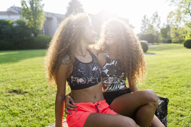 Happy twin sisters looking at each other at backlight — Stock Photo