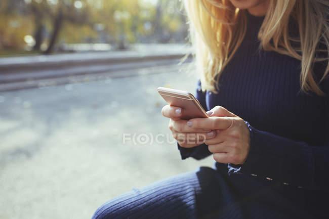 Блондинка со смартфоном в Осеннем городском парке — стоковое фото