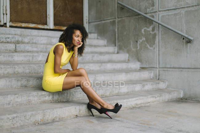 Модная бизнесвумен в желтом платье и высоких каблуках сидит на лестнице — стоковое фото