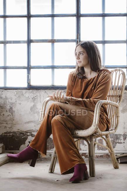 Дивна молода жінка сидить на кошику стільця в горищі — стокове фото