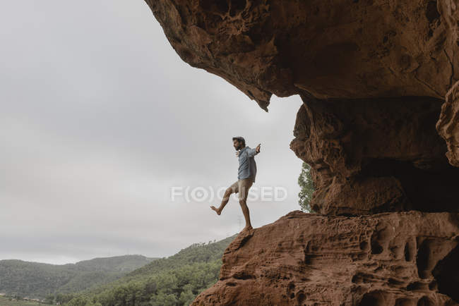 Young man balancing on the edge of an abyss — Stock Photo