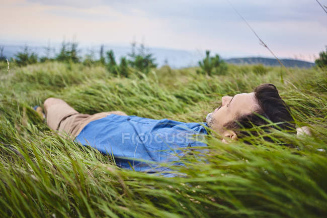 Relaxed man lying in grass — Stock Photo