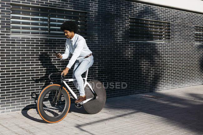Afro-americano homem montando sua bicicleta, usando smartphone — Fotografia de Stock