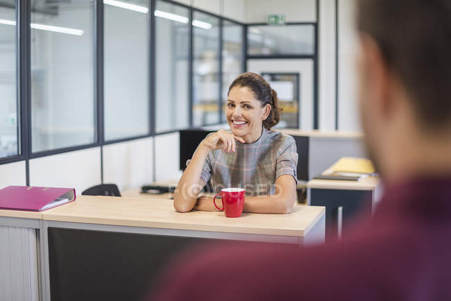 Female employee sitting at desk, talking to colleague — Stock Photo