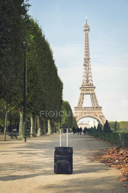Francia, Parigi, Champ de Mars, vista sulla Torre Eiffel con trolley bag in primo piano — Foto stock