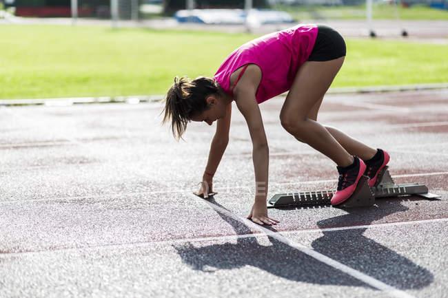 Подростковый бегун тренировочный старт на гоночной трассе — стоковое фото