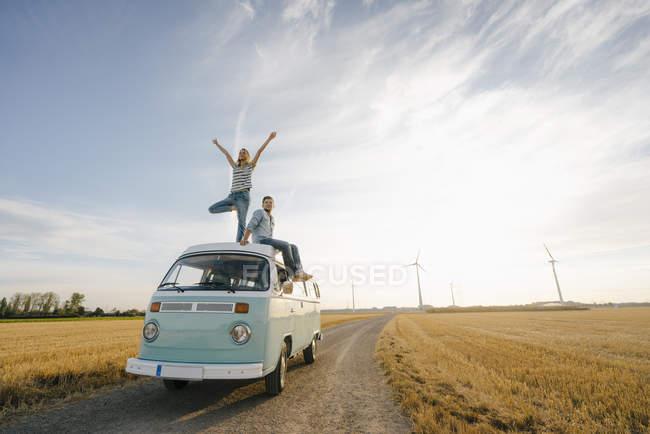 Молодая пара на крыше фургона в сельской местности — стоковое фото