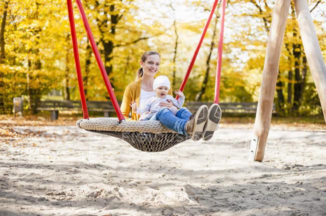 Baby-Mädchen sitzt im Herbst mit Mutter auf Schaukel — Stockfoto
