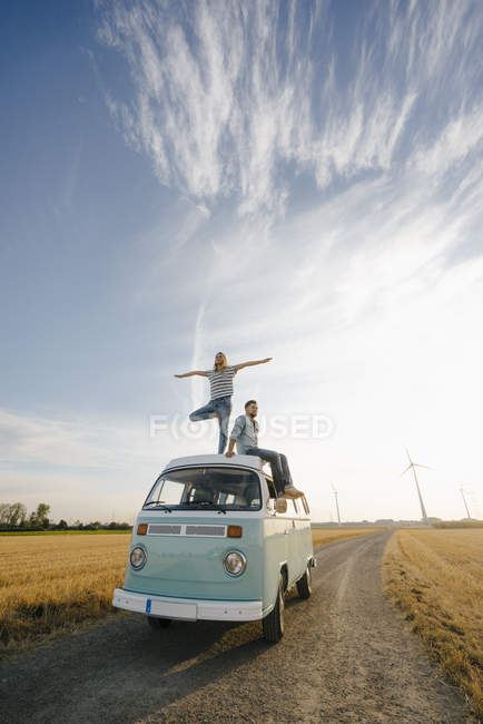 Young couple on roof of a camper van in rural landscape — Stock Photo