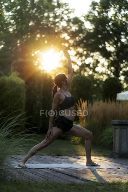 Mulher praticando ioga no jardim — Fotografia de Stock