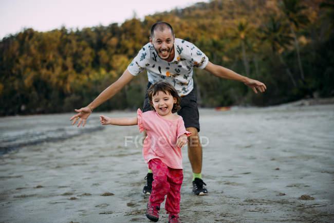 Австралия, Квинсленд, Маккей, Национальный парк Кейп-Хиллсборо, счастливый отец бежит за своей дочерью на пляже — стоковое фото