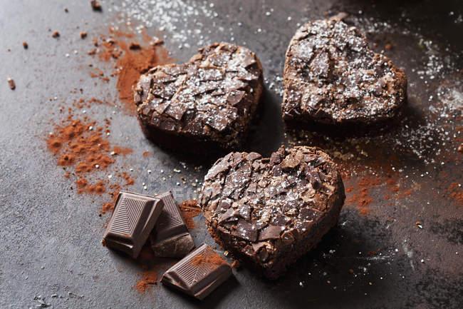 Trois brownies en forme de cœur et chocolat sur métal — Photo de stock