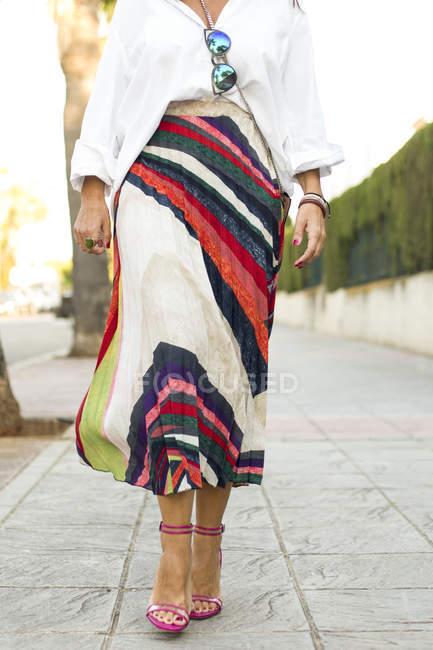 Низкая часть модной женщины, идущей по тротуару — стоковое фото