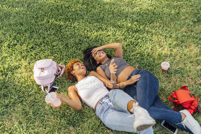 Zwei unbeschwerte Freundinnen entspannen sich in einem Park — Stockfoto