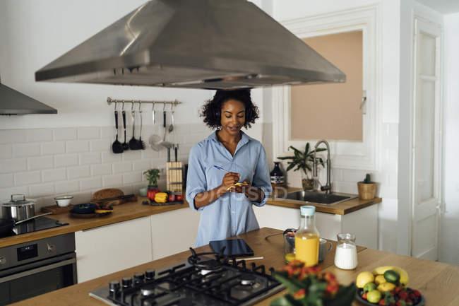 Mulher em sua cozinha na manhã, escrevendo notas — Fotografia de Stock