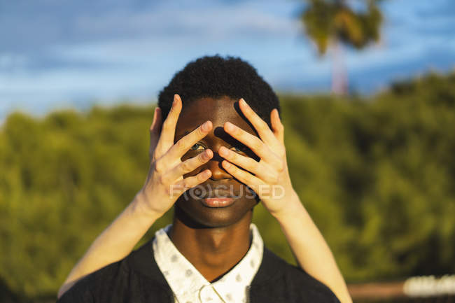 Hands covering eyes of a young black man — Stock Photo