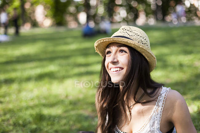 Retrato de uma jovem feliz em um parque assistindo algo — Fotografia de Stock
