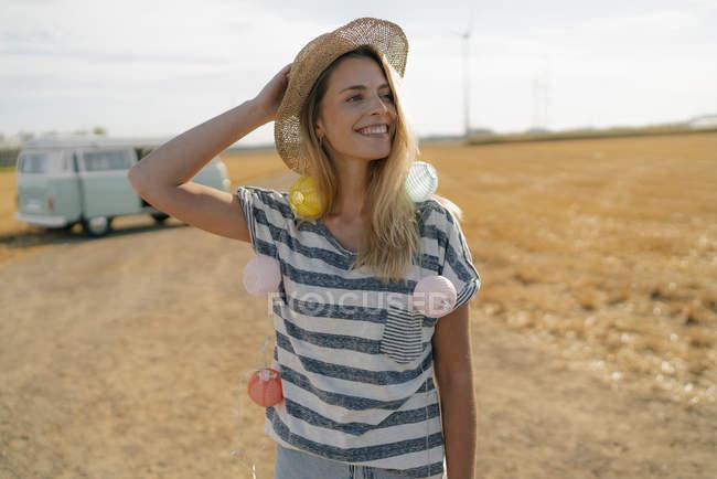 Happy young woman at camper van in rural landscape — стокове фото