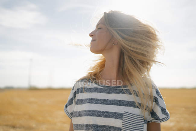 Portrait of smiling young woman in rural landscape waving blond hair — Stock Photo