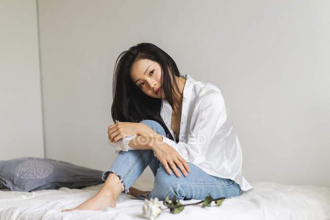 Портрет привлекательной молодой женщины, сидящей на кровати с белой розой — стоковое фото
