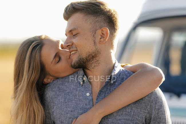 Женщина целует мужчину с закрытыми глазами на фургоне в сельской местности — стоковое фото
