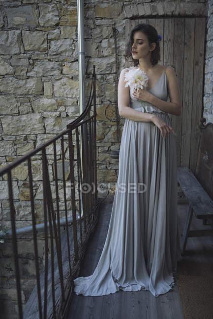 Jovem mulher vestindo vestido cinza e segurando uma flor — Fotografia de Stock