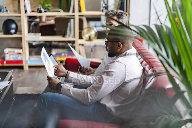 Dos empresarios que utilizan ordenador portátil y discuten documentos sobre el sofá en la oficina de loft. - foto de stock