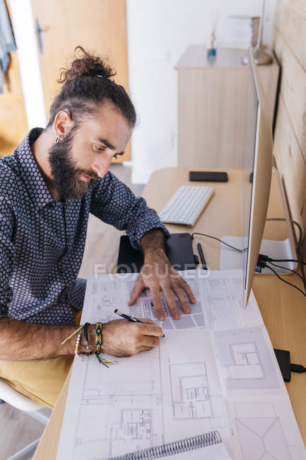 Young architect working at home with blueprints — Stock Photo
