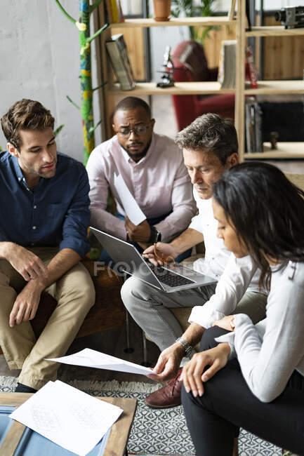 Equipo de negocios con ordenador portátil y discusión de documentos en la oficina de loft - foto de stock