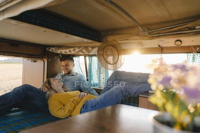 Happy young couple relaxing inside camper van — Stock Photo