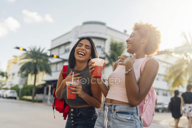 USA, Florida, Miami Beach, two happy female friends having a soft drink in the city — Stock Photo