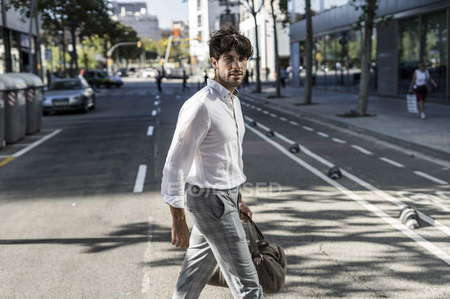 Young man in city crossing street road — Stock Photo