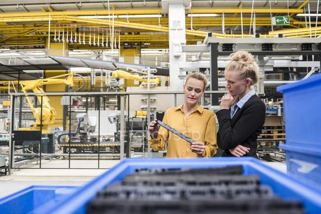 Two women examining workpiece in factory — Stock Photo