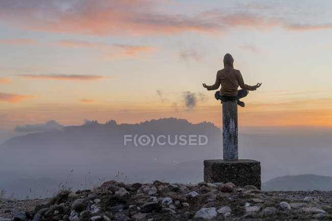 Испания, Барселона, природный парк Сан-Ллоренк, человек, сидящий в позе йоги на шесте на закате — стоковое фото