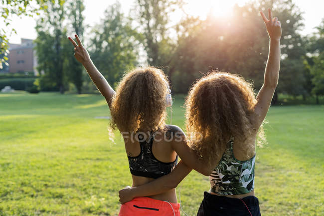 Back view of twin sisters standing side by side in a park and showing victory signs — Stock Photo