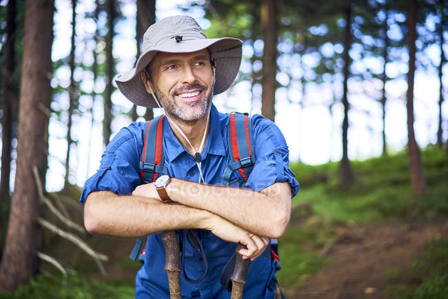 Smiling man having a break from hiking in the forest — Stock Photo