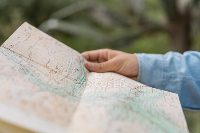 Young man standing in nature, looking at map — Stock Photo