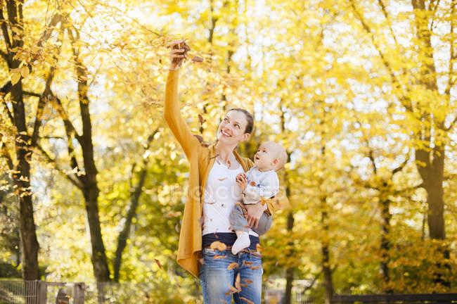 Madre e bambina si divertono con le foglie in autunno — Foto stock