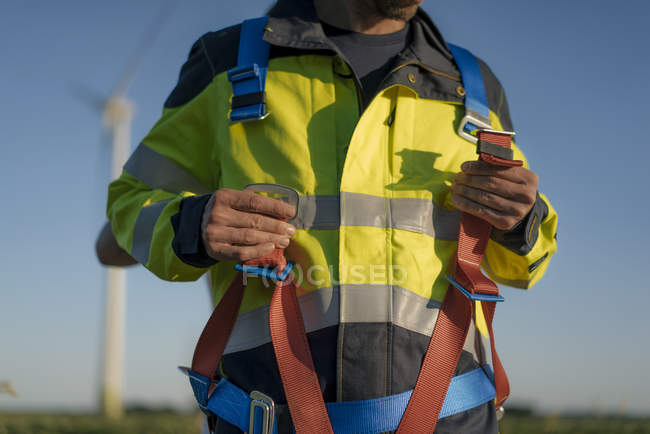 Close-up of technician at a wind farm putting on climbing harness — Stock Photo