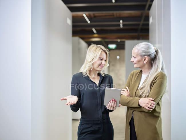 Two businesswomen sharing tablet on office floor — Stock Photo