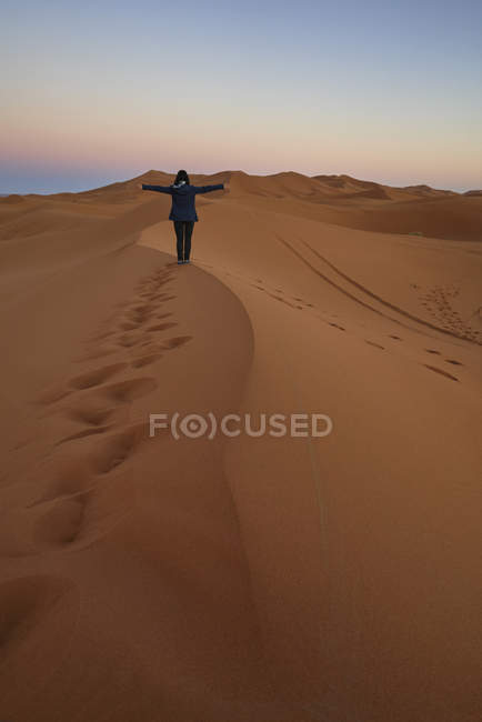 Morocco, back view of woman standing on desert dune at twilight — Stock Photo
