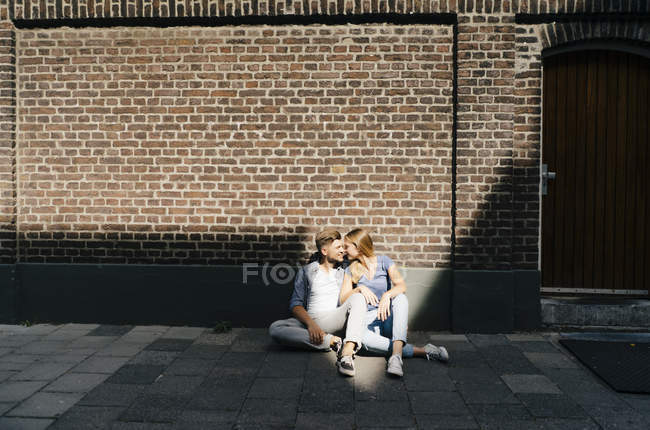 Netherlands, Maastricht, young couple having a break in city sitting on sidewalk at brick wall of building — Stock Photo