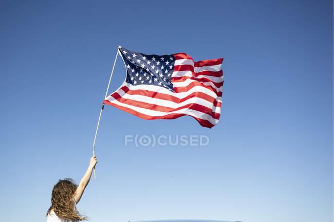 Ragazza che tiene bandiera americana sotto il cielo blu — Foto stock